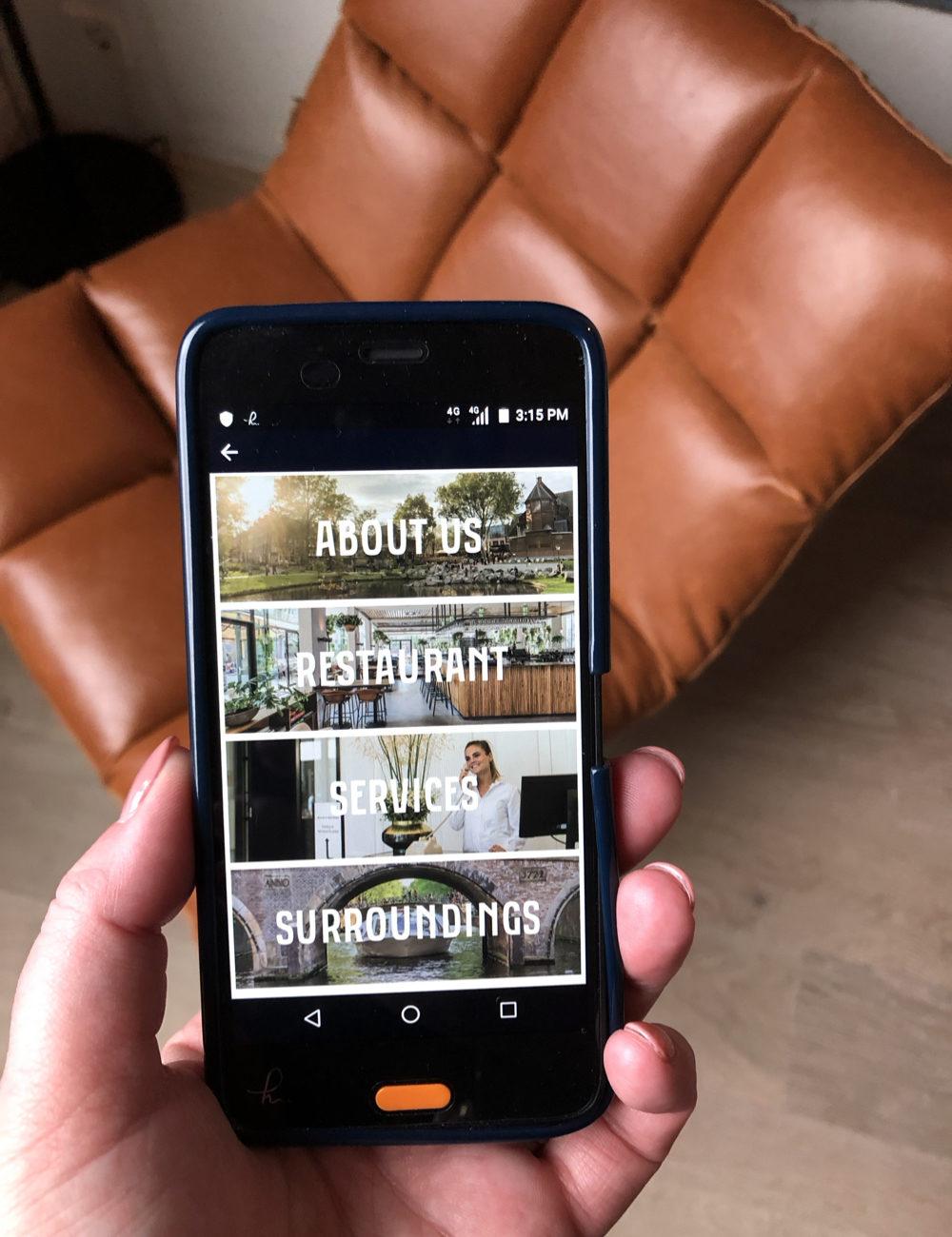 Een smartphone met afbeelding van de app van Hotel Arena