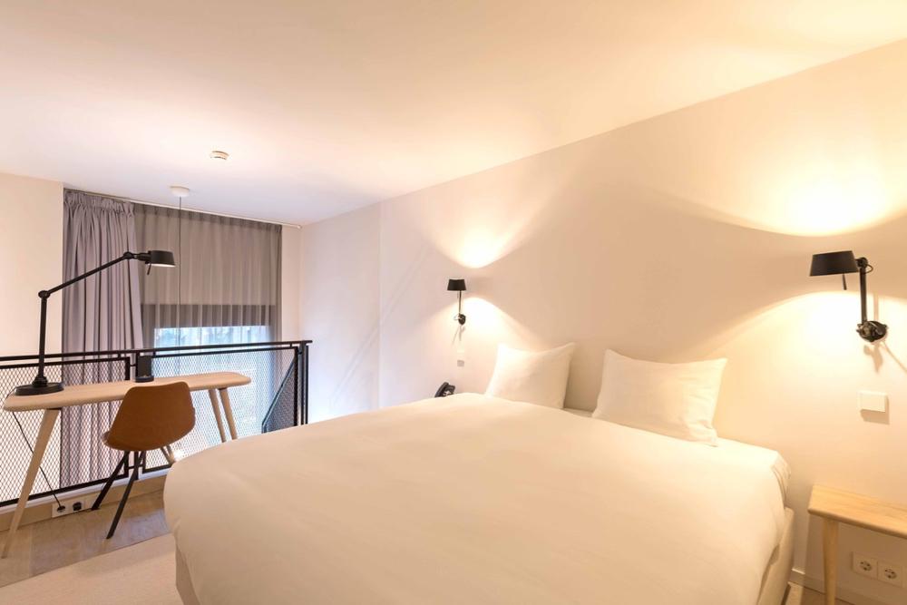 Tweepersoons bed op de vide van een hotelkamer