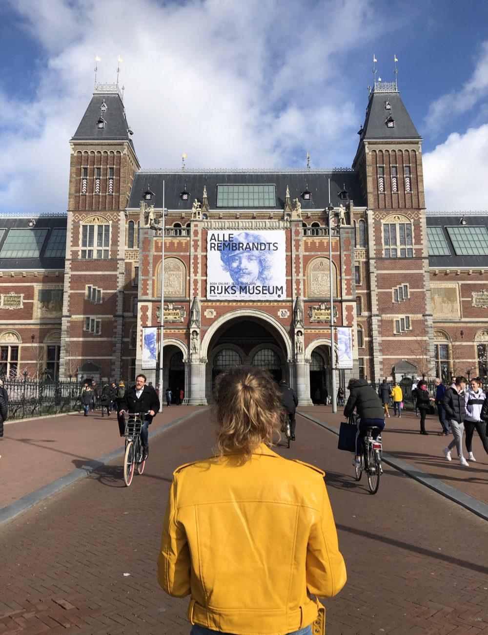 Een meisje met gele leren jas voor het Rijksmuseum in Amsterdam