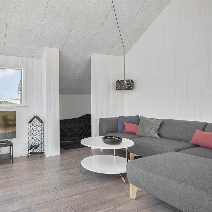 Witte woonkamer met grijze hoekbank en rond wit tafeltje
