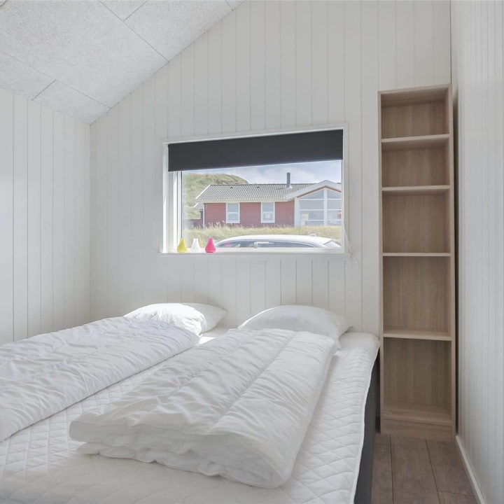 Witte slaapkamer met smal raam en onopgemaakt bed