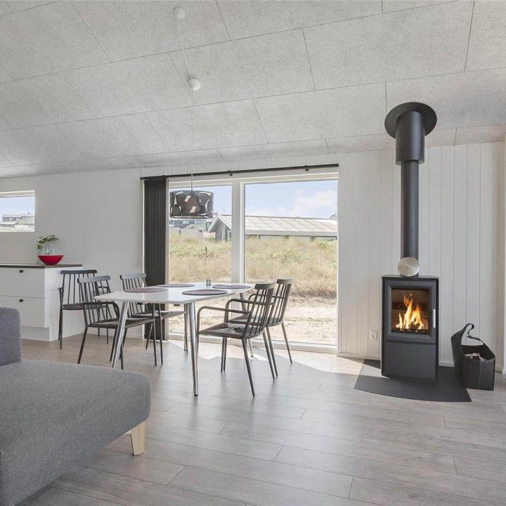 Ruime en lichte woonkamer met grote ramen, brandende houtkachel en eethoek