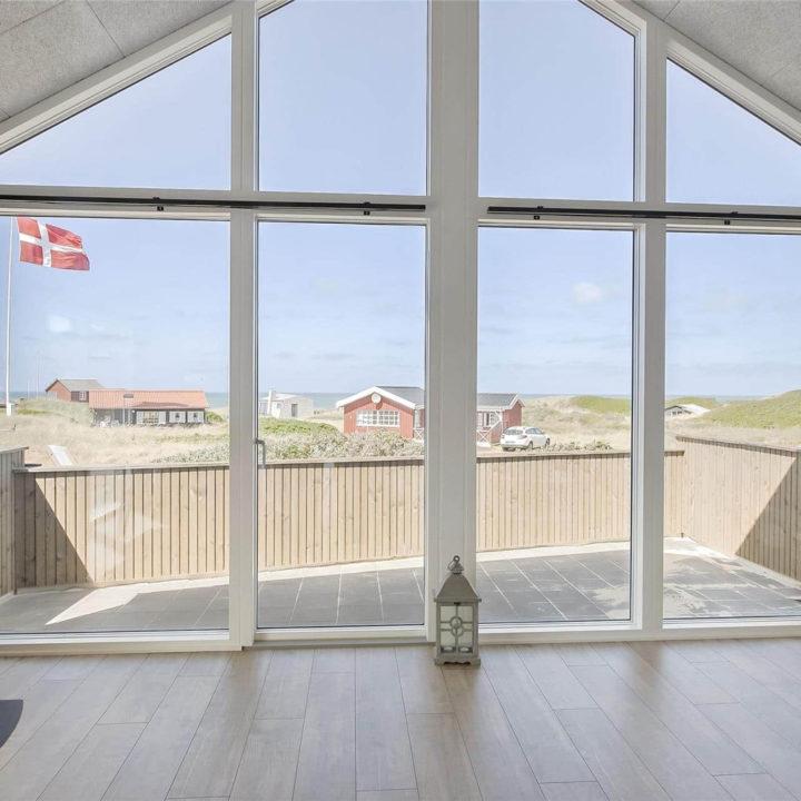 Grote glazen gevel in woonkamer, met zicht op duinen en zee