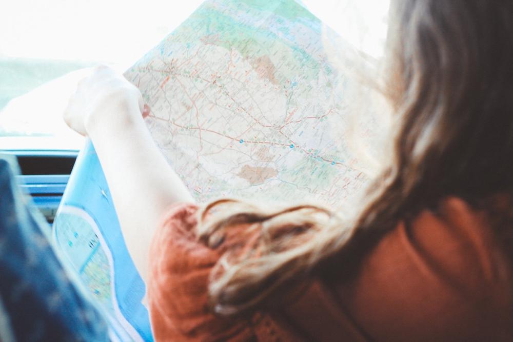 Een vrouw in een auto houdt een landkaart vast