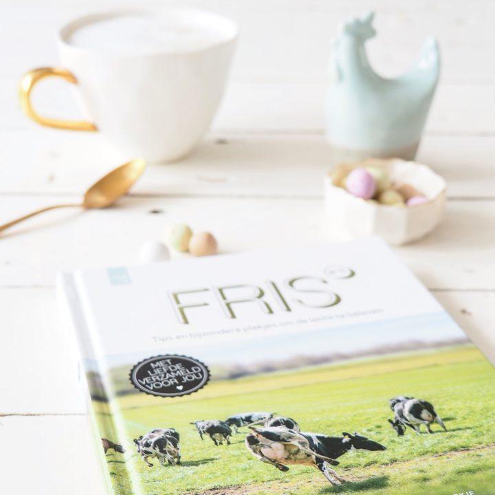 Het boek Fris op een witte tafel, met cappuccino en paaseitjes