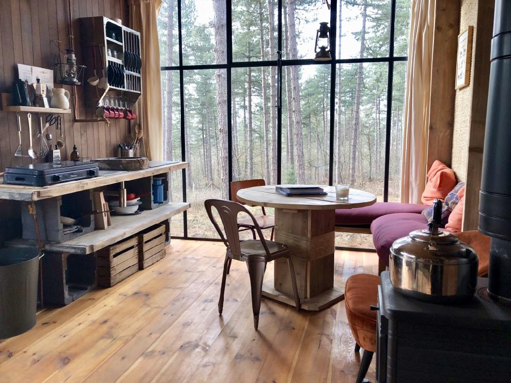 Groot stalen raam met zicht op het bos, ervoor een zithoek met ronde houten tafel en robuuste keuken