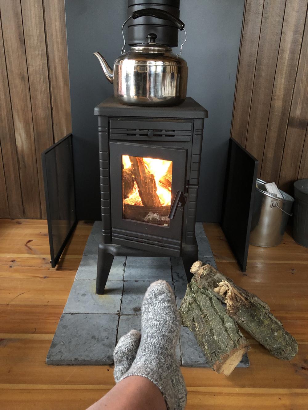 Grijze sokken voor de brandende houtkachel