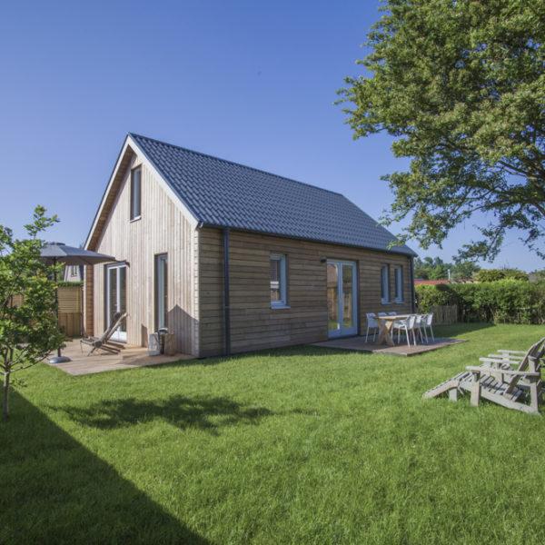Buitenaanzicht van houten huis in tuin met groot grasveld