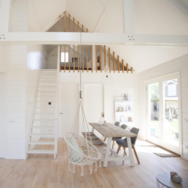 Lichte zonnige grote ruimte met hangstoel en lange eettafel