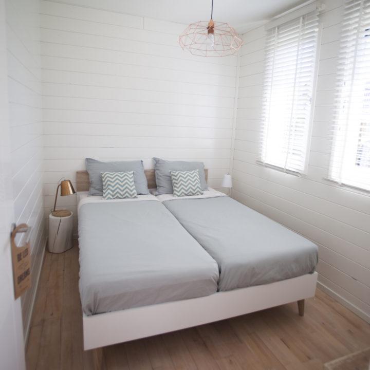 Tweepersoons slaapkamer, helemaal wit, met opgemaakt bed