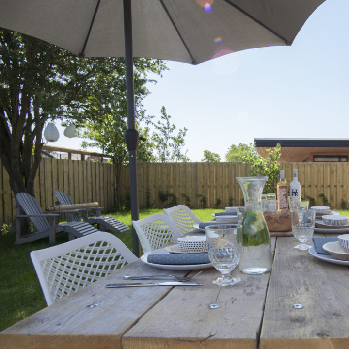 Gedekte tafel in de tuin, onder de parasol