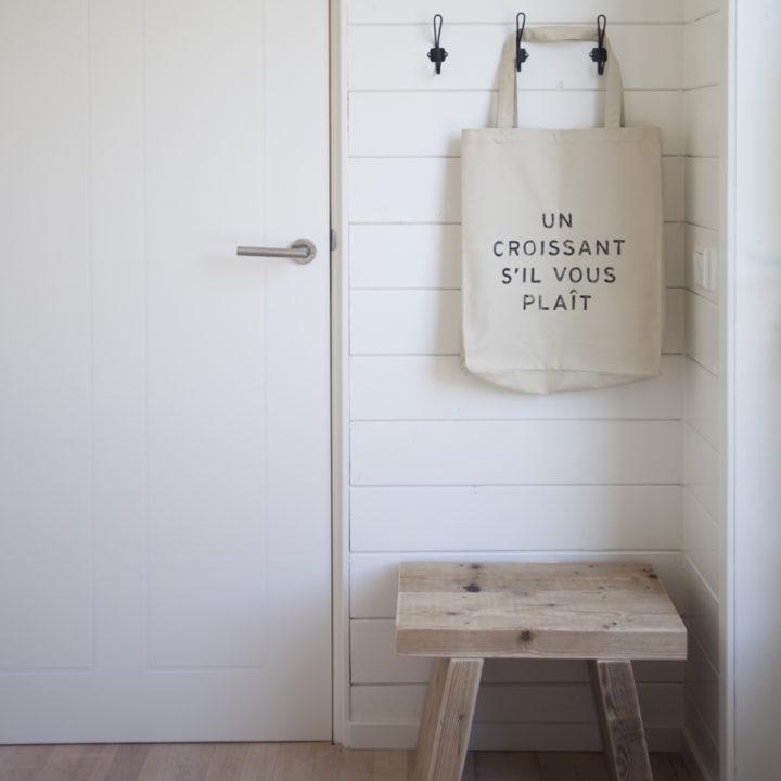 Witte hal met houten krukje en linnen zak aan de wand met de tekst un croissant s'il vous plait