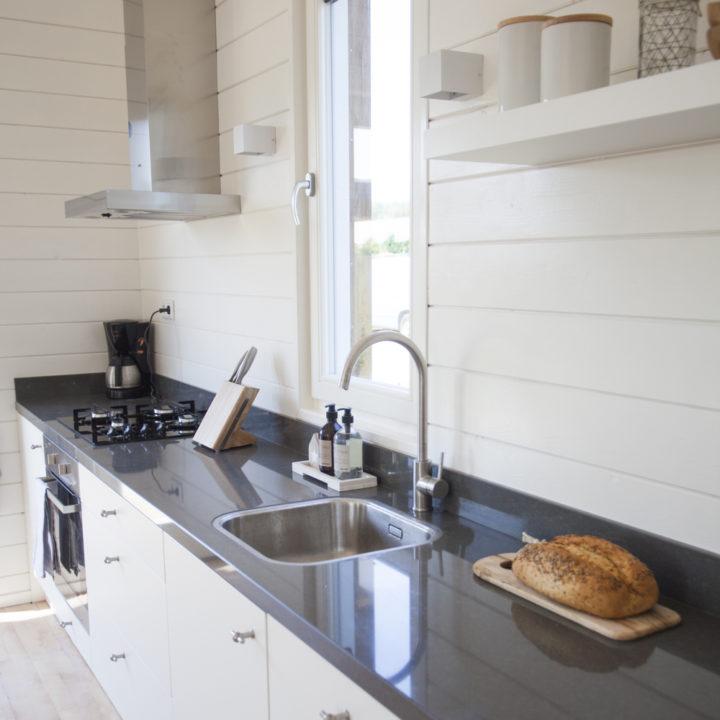 Lange rechte keuken met witte kastjes en grijs aanrechtblad