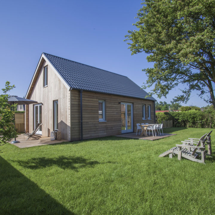 Houten vakantiehuis met grasveld met ligstoelen en twee terrassen aan huis