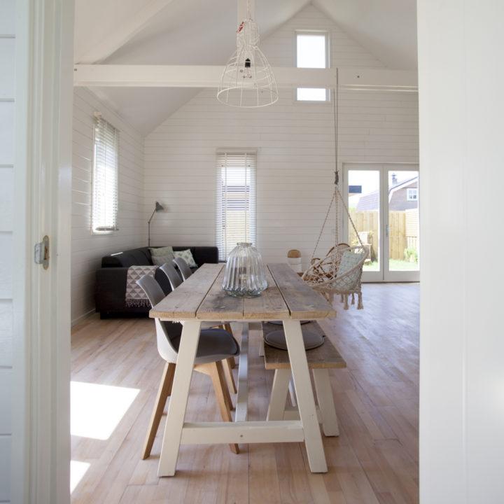 Lange eettafel met stoelen en zicht op zithoek op achtergrond