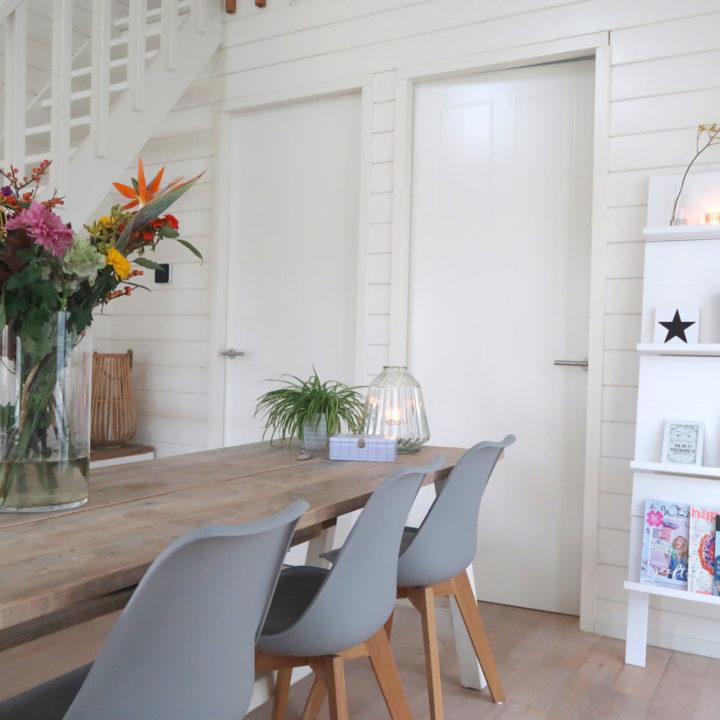 Lange houten eettafel met grijze kuipstoelen en bos bloemen op tafel