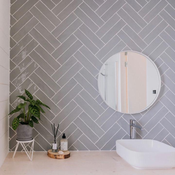 Badkamer met grijze tegels, een plantje en ronde spiegel