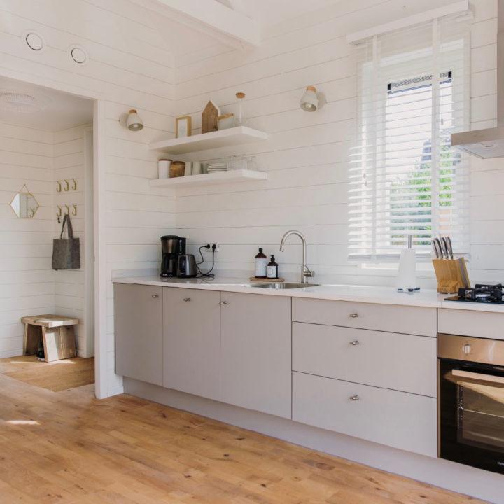 Moderne lichte keuken, in lichtgrijs met houten achterwand