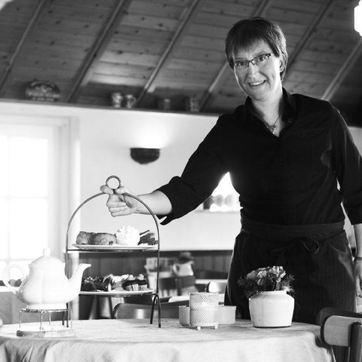 Zwart wit foto van de gastvrouw van het theehuis, houdt een etagere vol lekkers vast