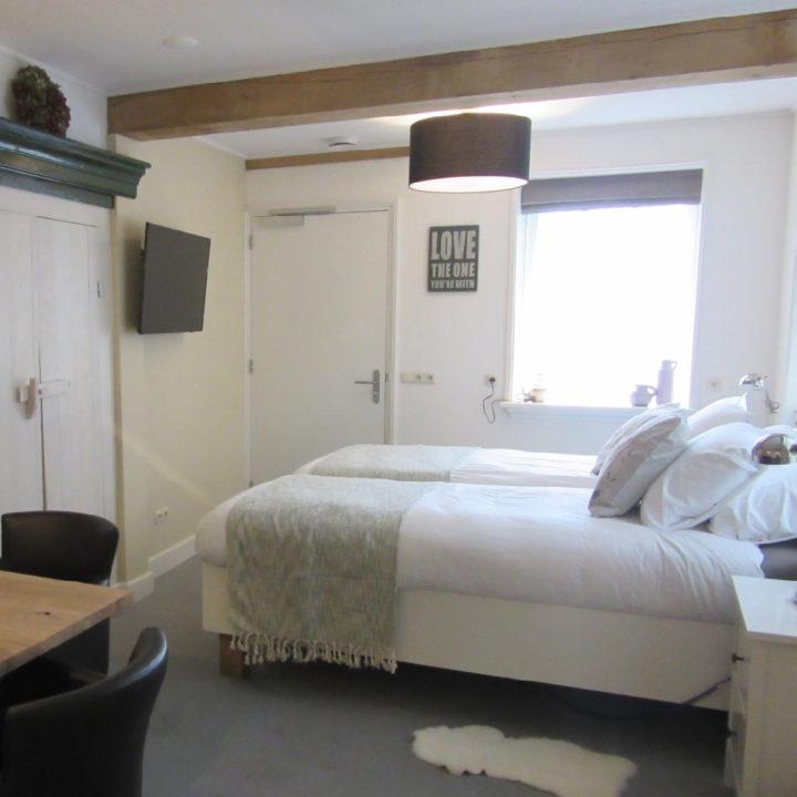 Landelijke B&B kamer met wit opgemaakt bed