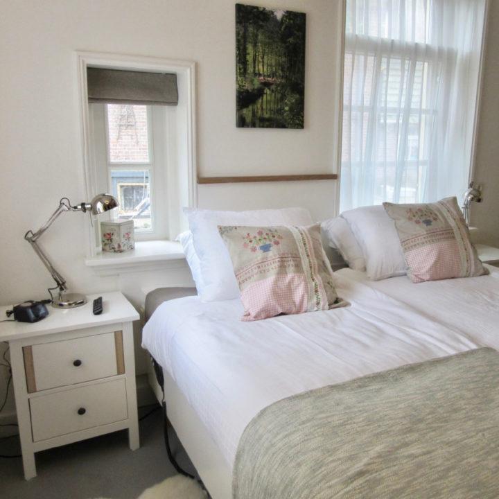 Romantisch opgemaakt tweepersoonsbed met nachtkastje en bedlamp
