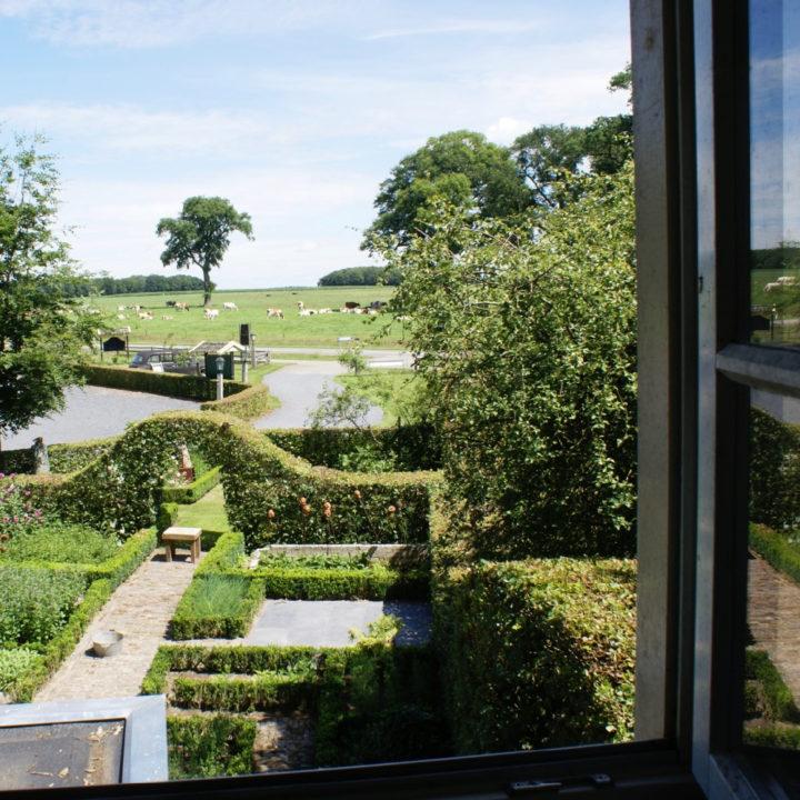 Zicht vanuit open raam op de tuin en weilanden met koeien