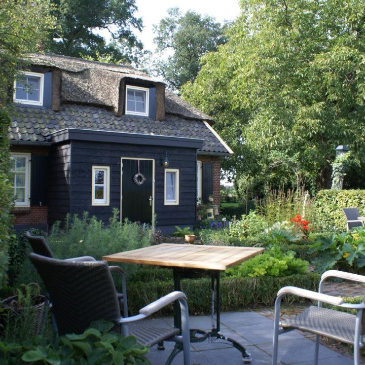 Schattig boerderijtje met rieten dak en zwart houten entree