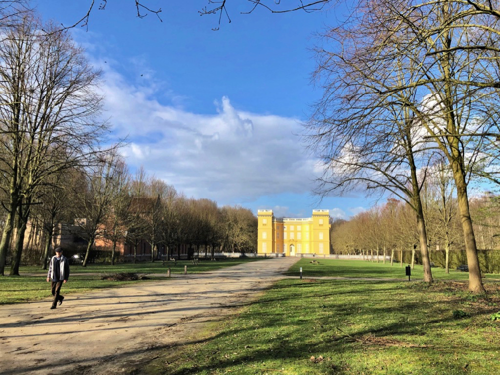 Een geel gekleurd kasteel in een parkachtige omgeving