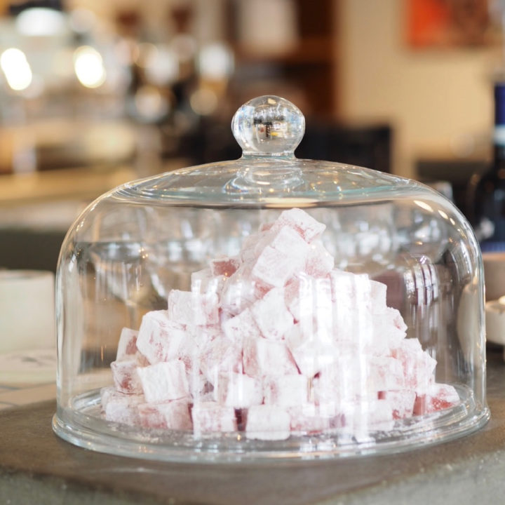 Close up foto van een glazen stolp en roze snoepjes eronder