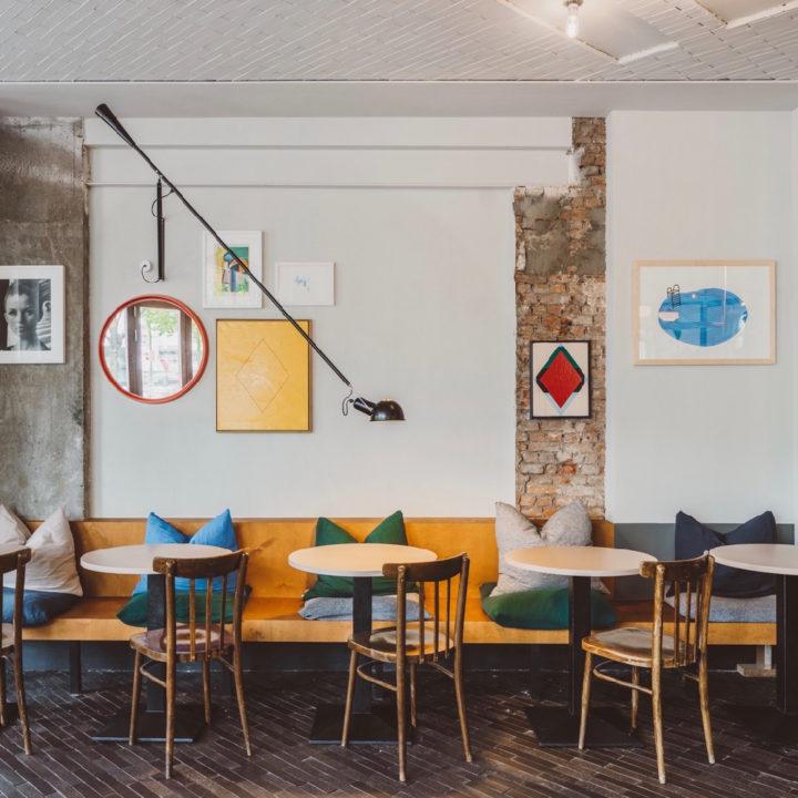Houten bank langs de muur met ronde tafeltjes en gekleurde kussens op de bank