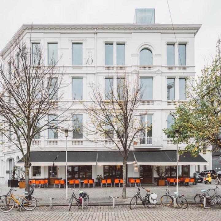Witte gevel van een hotel, oranje stoelen op het terras