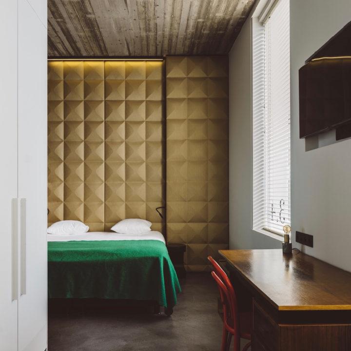 Hotelkamer met gouden wand, groene sprei op bedf en houten bureau met rode stoel