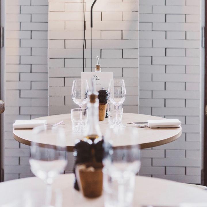 Ronde gedekte tafels met witte stenen muur
