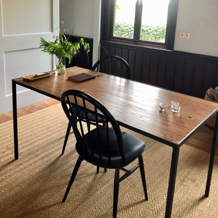 Houten tafelblad met stalen frame en zwarte eetstoelen