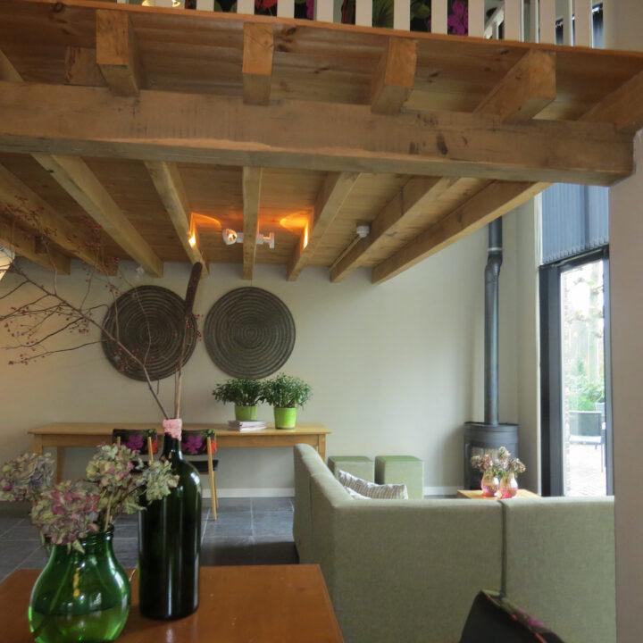 Woonkamer met stoere houten balken vide