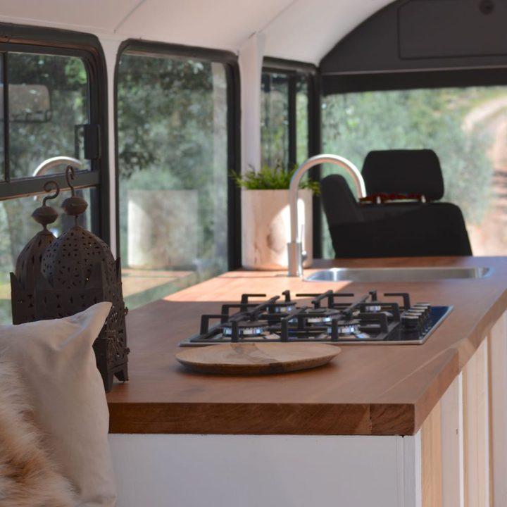 Schoolbus omgebouwd tot accommodatie, keukenblok met gasfornuis
