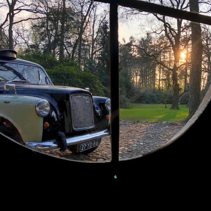 Oldtimer gezien door een raam, bij zonsondergang