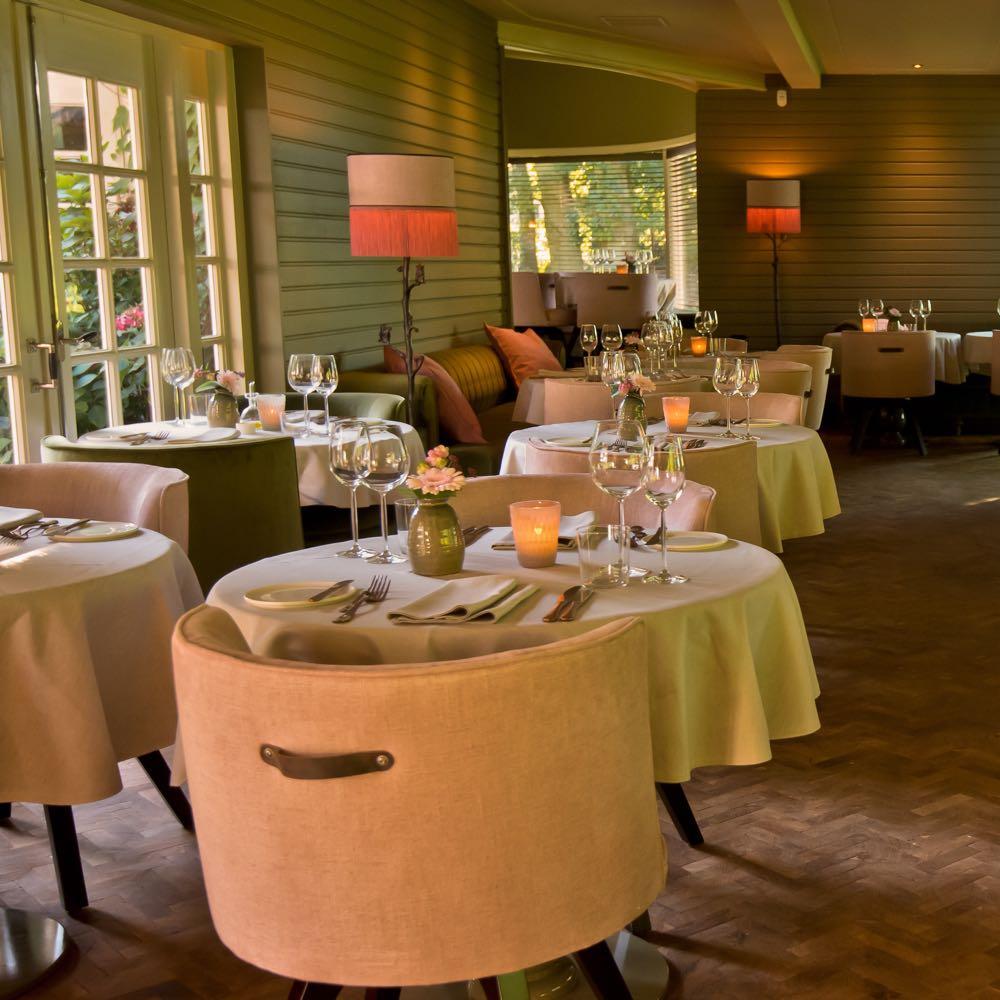 Ronde gedekte tafels met roze fauteuils
