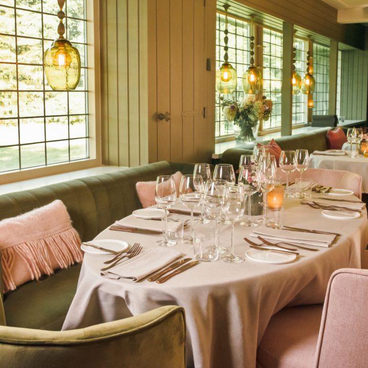 Gedekte tafels met roze stoelen, groene banken langs de wand en glas in lood ramen