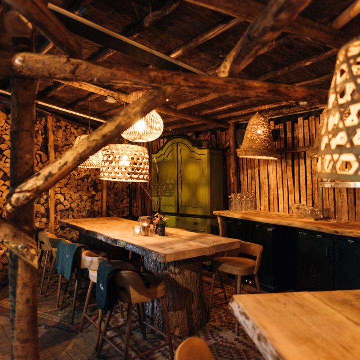 Houten tafels en stoere barkrukken in schuur