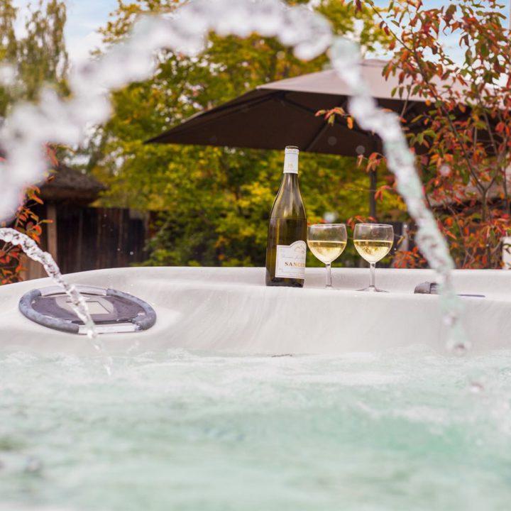 Bubbelend water in de jacuzzi met fles wijn op de rand