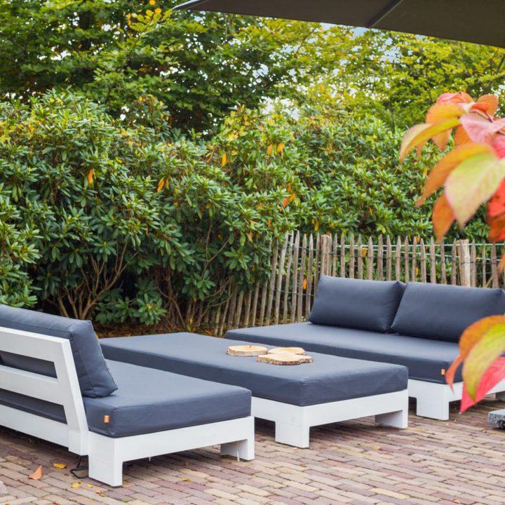 Witte banken met loungekussens in de tuin