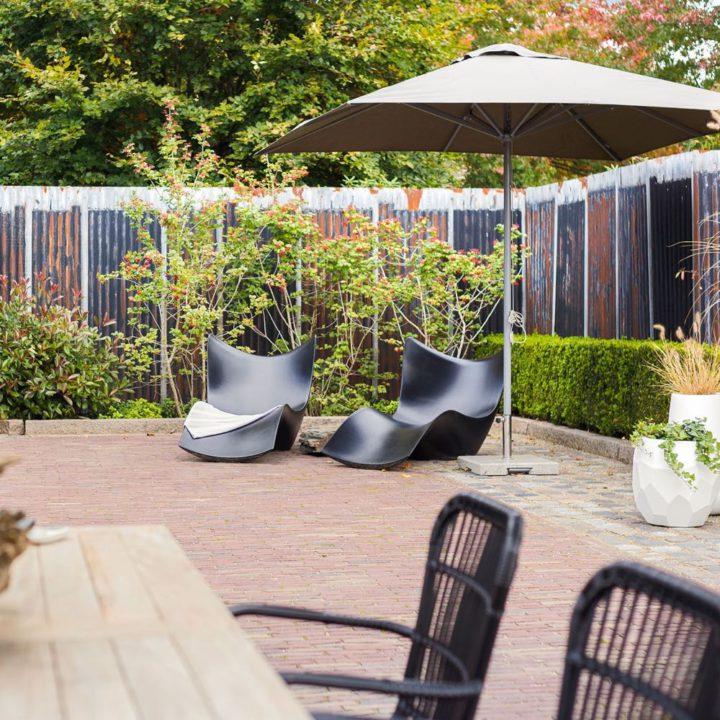 Terras met parasol, eettafel en stoelen en ligstoelen