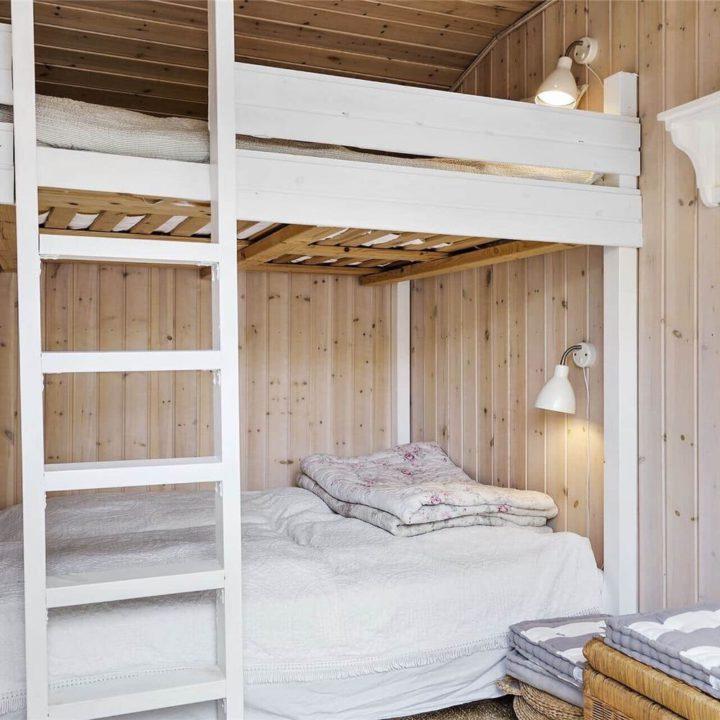 Slaapkamer met houten wanden en stapelbed