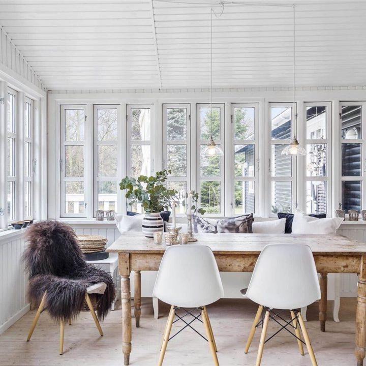 Lichte eethoek met grote ramen, houten eettafel en witte stoelen met bontje erop