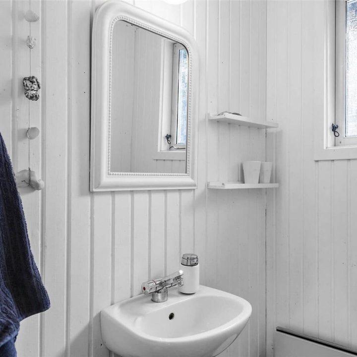 Witte badkamer met wastafel en witte spiegel