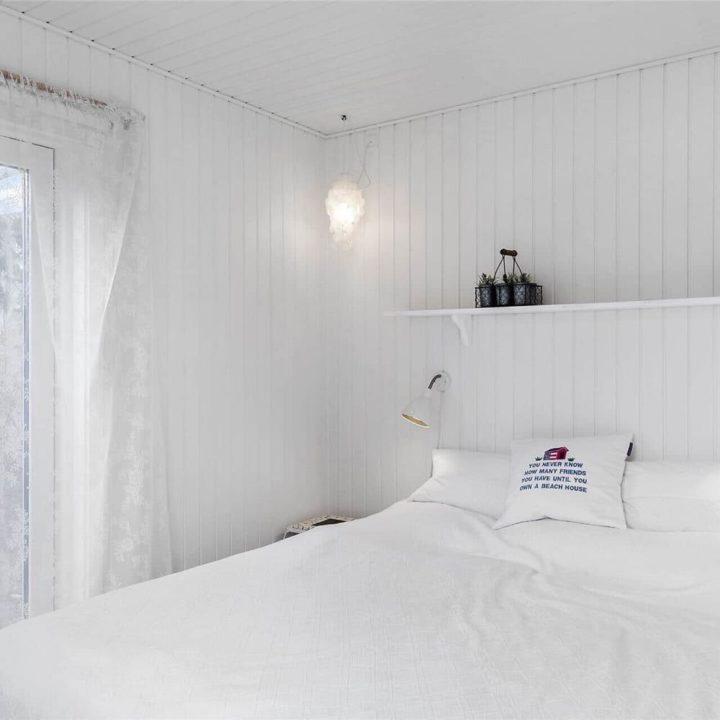 Slaapkamer met witte houten wanden en wit tweepersoons bed