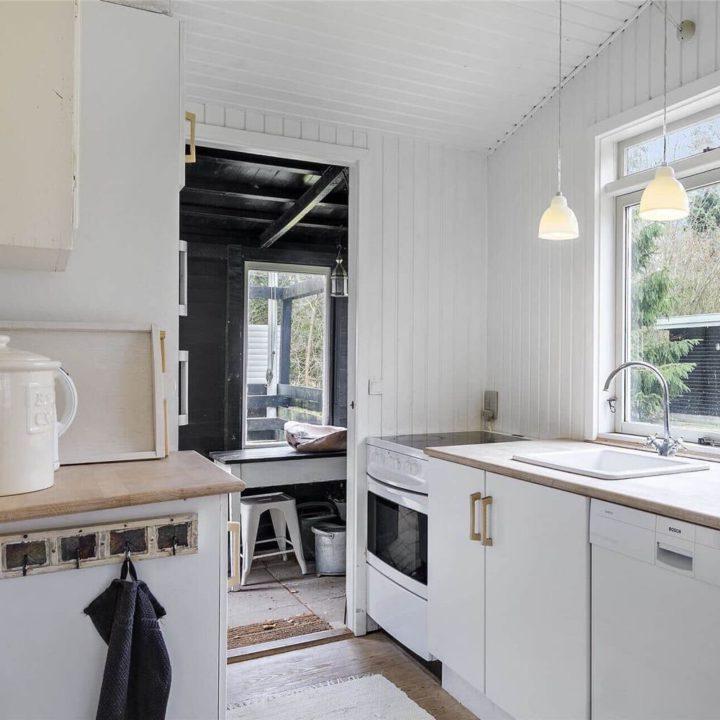Eenvoudige keuken met witte houten wanden en houten aanrechtblad