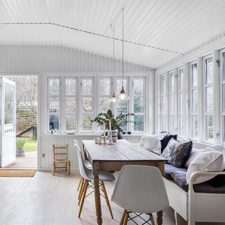 Houten eettafel met witte kuipstoelen en een Zweedse klepbank met kussens