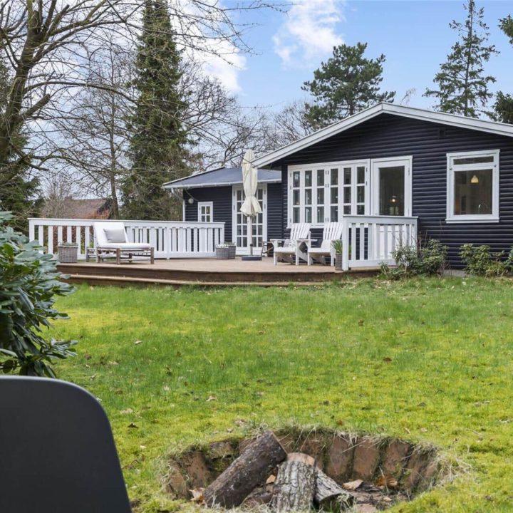 Zwart houten vakantiehuis met vuurschaal in het gras